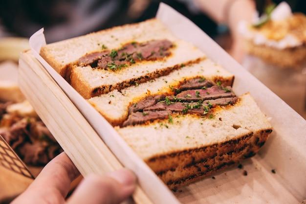 Close up of japanese medium rare wagyu sandwich served in wooden box Premium Photo