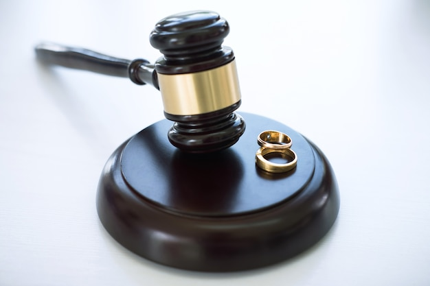 Close up of judge gavel deciding on marriage divorce and two golden marriage ring Premium Photo