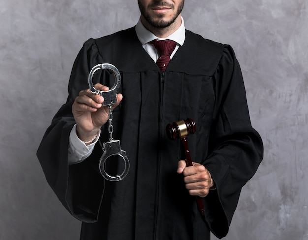 Close-up judge with handcuffs and gavel Free Photo