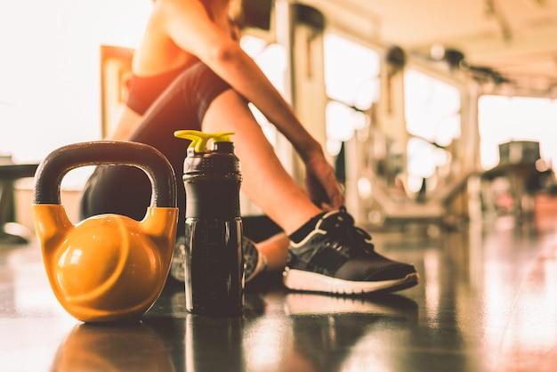 체육관 체력 단속에 여자 운동 운동으로 Kettlebells을 닫습니다 스포츠 후 휴식 프리미엄 사진