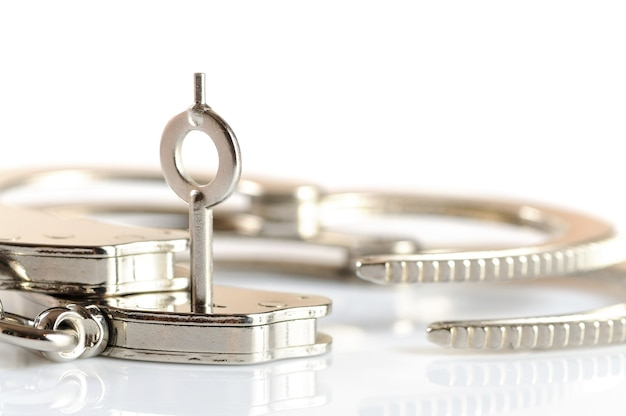 Close-up of a key opens a handcuff lying on a white table. concept release from imprisonment. freedom from stereotypes and complexes. advertising space Premium Photo