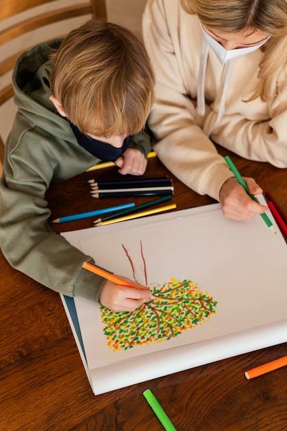 Bambino del primo piano che disegna all'interno Foto Gratuite