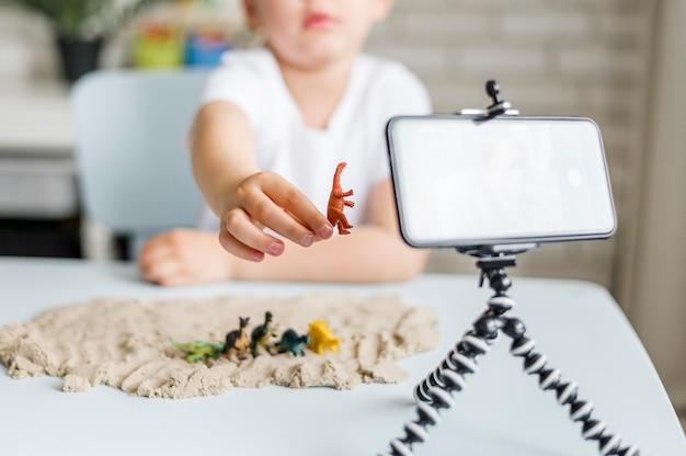 Dinosauro della tenuta del bambino del primo piano Foto Gratuite