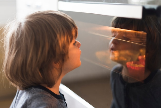 Close-up kid looking at oven Free Photo