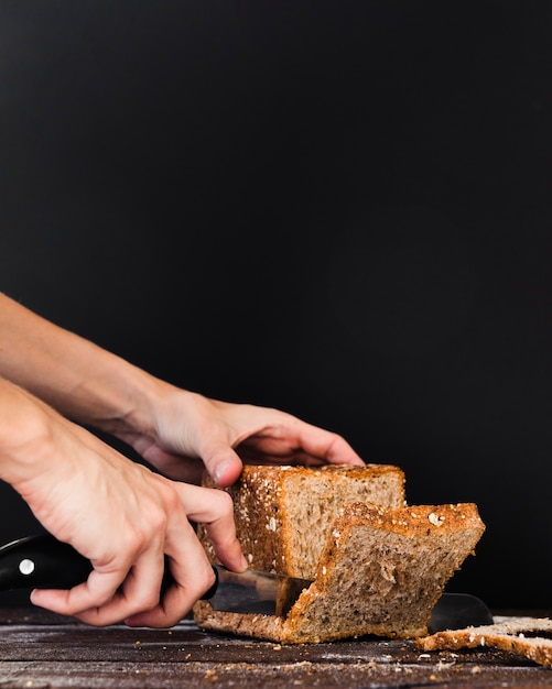 Close-up knife cutting bread loaf Free Photo