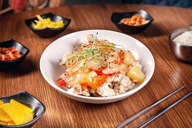 木製の背景にキムチと韓国の伝統的な食べ物を閉じます。玉ねぎ、レッドソース、ゴマ、鶏肉入り韓国米。伝統的なアジア料理。ランチ。健康食品 Premium写真