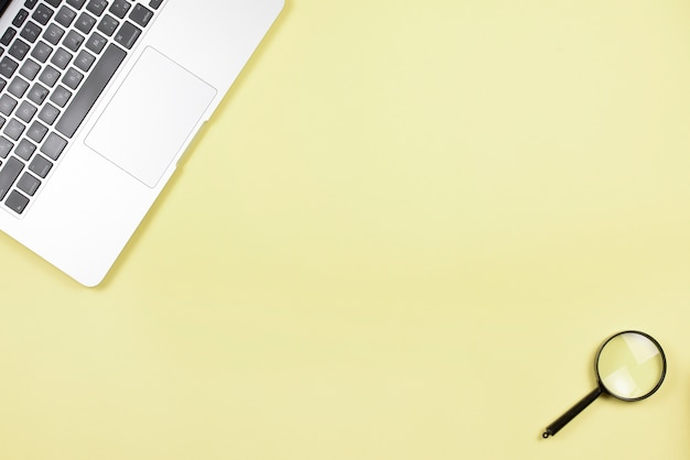 Close-up laptop and magnifying glass on yellow background Free Photo