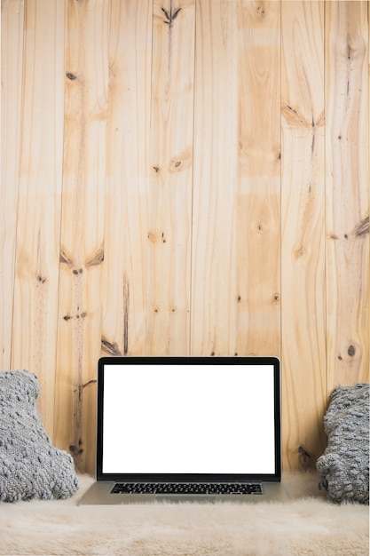 Close-up of laptop and pillow on soft fur against wooden backdrop Free Photo