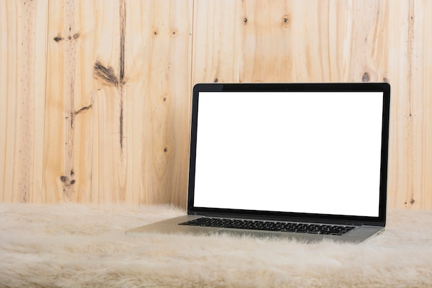 Close-up of laptop on soft fur in front of wooden wall Free Photo