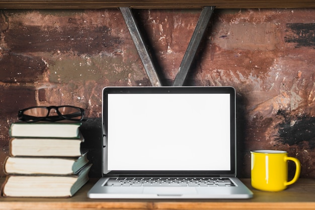 Close-up of laptop; stacked books; spectacles and cup on wooden shelf Free Photo