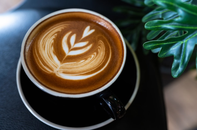 Close up of latte art coffee on wooden table Premium Photo