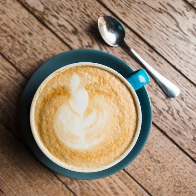Primo piano del caffè del latte con arte creativa del latte su fondo strutturato di legno Foto Gratuite