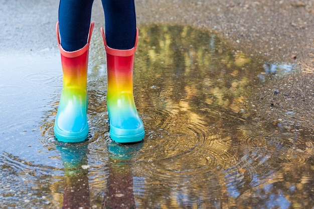 Close up of legs of child girl with rainbow rubber boots jump in puddle on an autumn walk. Premium Photo