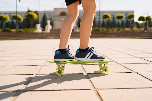 モーションで緑のスケートボードに乗って青いスニーカーで足を閉じます。若者のアクティブな都会のライフスタイル、トレーニング、趣味、活動。子供のためのアクティブなアウトドアスポーツ。子供のスケートボード。 無料写真