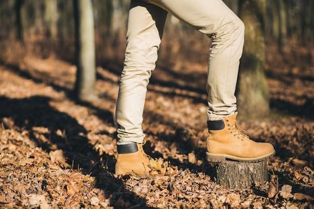 秋の森、アクティブな観光客、寒い季節に自然を探索する履物、履物を旅行する流行に敏感な男の靴を追跡する足を閉じる 無料写真