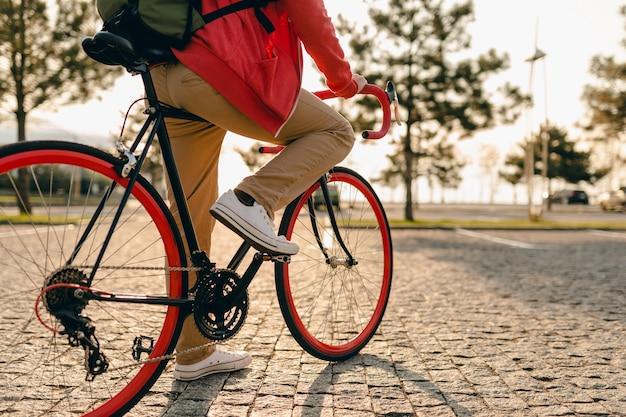 Chiudere le gambe in scarpe da ginnastica e le mani sul volante dell'uomo barbuto stile hipster in felpa con cappuccio rossa e pantaloni beige cavalcando da solo con lo zaino in bicicletta viaggiatore zaino in spalla sano stile di vita attivo Foto Gratuite