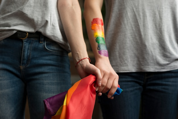 Close-up of lesbian couple holding lbgt flag in hands Premium Photo