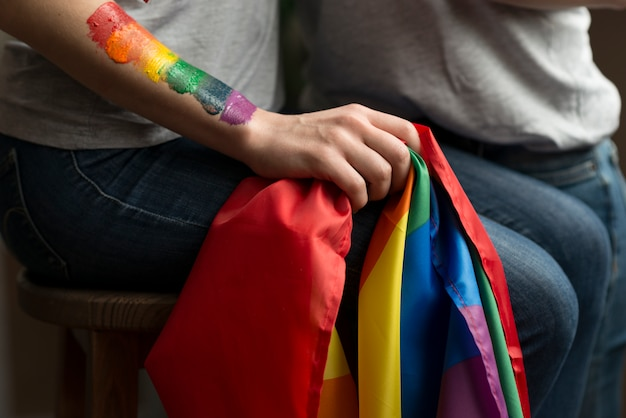 Close-up of lesbian young couple holding lbgt flag in hand Free Photo
