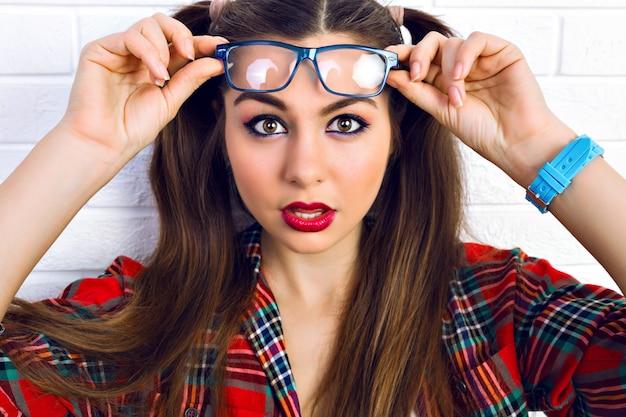 Закройте вверх по портрету моды образа жизни молодой битник женщины с ярким составом и двумя забавными хвостиками, удивленными положительными эмоциями. Бесплатные Фотографии