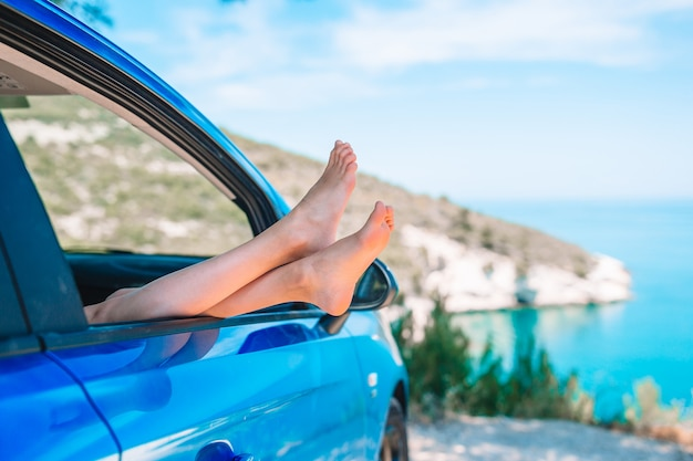 Close up of little girl feet showing from car window background sea Premium Photo