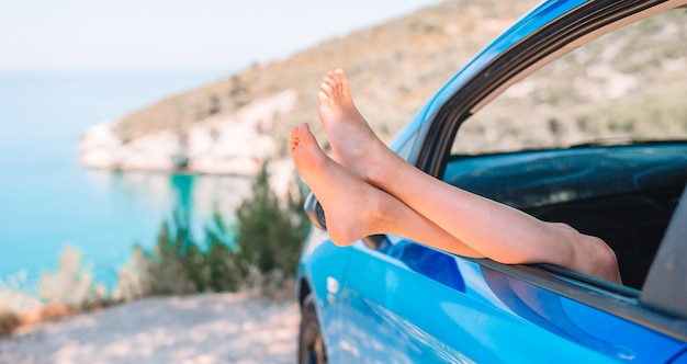 Close up of little girl feet showing from car window Premium Photo