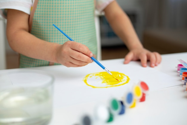 Close-up little girl with apron painting Free Photo