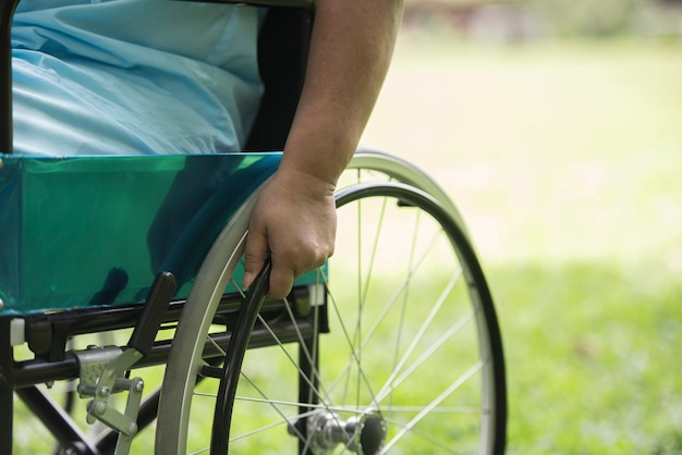 Close up lonely elderly woman sitting on wheelchair at garden in hospital Free Photo