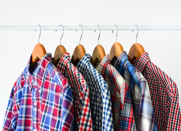 Close up of long sleeve red and blue checkered shirt on wooden hanger over white Premium Photo