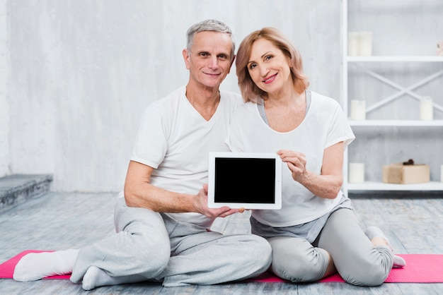 Close-up of a loving couple holding black screen digital tablet Free Photo