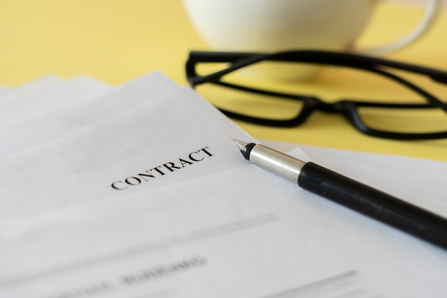 A close up macro view of a contract document with eye glasses and a pen Premium Photo
