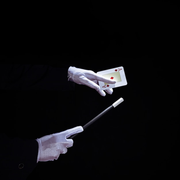 Close-up of magician performing trick on playing card with magic wand Free Photo