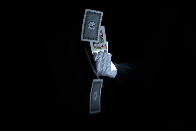 Close-up of magician's hand throwing playing cards against black background Free Photo