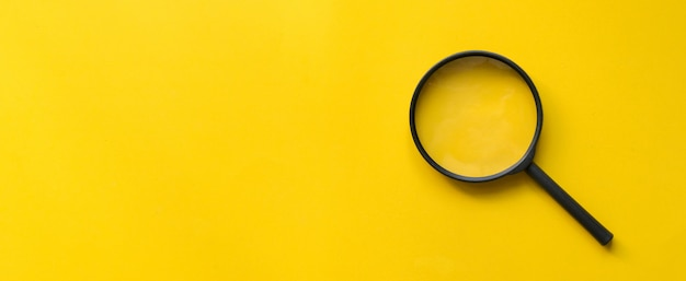Close up magnifier glass on yellow background Premium Photo