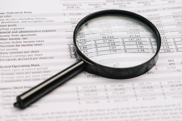 Close-up of magnifying glass on balance sheet Free Photo