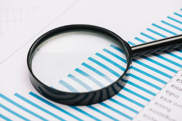 Close-up of a magnifying glass on blue bar graph Free Photo