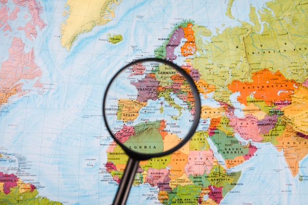 Map Of The World Close Up.Close Up Of Magnifying Glass In Front Of World Map Photo