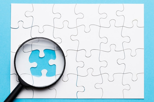 Close-up of magnifying glass on missing puzzle over blue background Free Photo