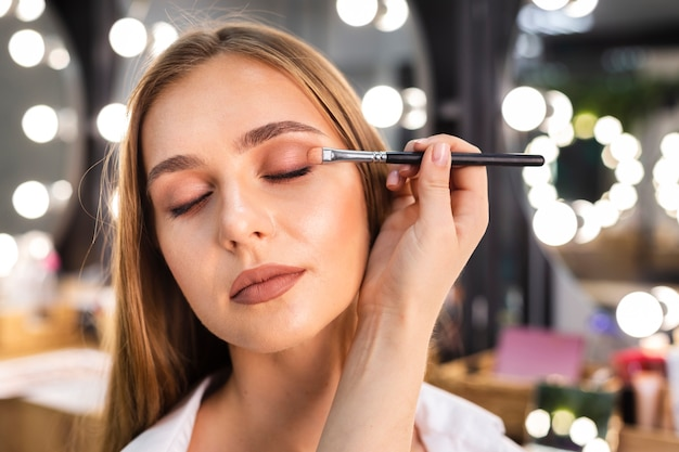 Close up make-up artist applying eyeshadow on woman with brush Free Photo