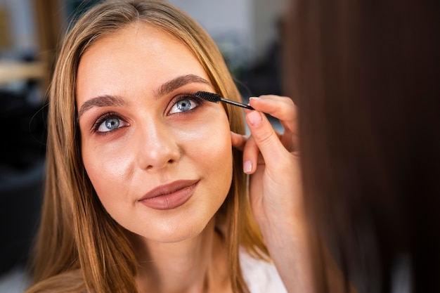 Close up make-up artist applying mascara on woman Free Photo