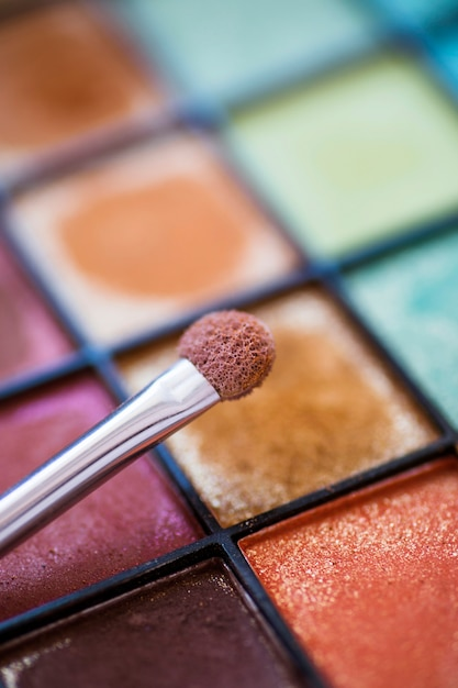 Close Up Of Makeup Brush Over Colorful Eye Shadow Palette Photo