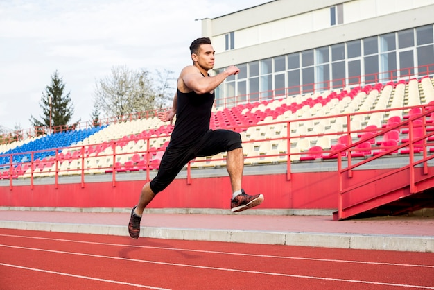 Close-up of a male athlete running on racing track at stadium Free Photo