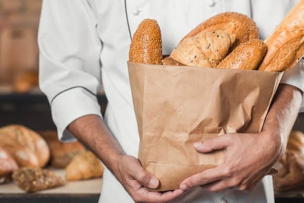 Close-up of male baker's hand holding baked bread in an paper bag Free Photo