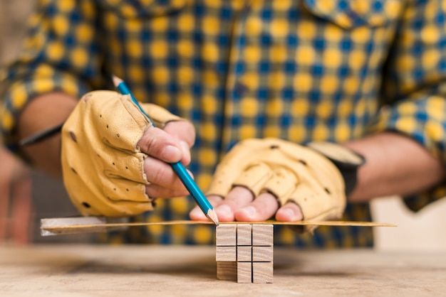 Close-up of a male carpenter's hand making measurement on wooden block Free Photo