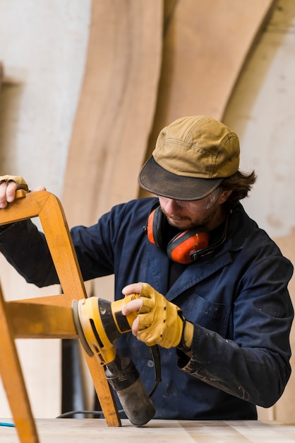 Close-up of a male carpenter sanding furniture with power tool on workbench Free Photo