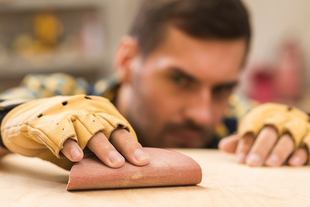 Close-up of a male carpenter wearing protective gloves in hand rubbing sandpaper on wooden plank Free Photo