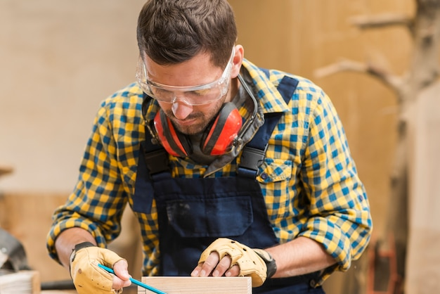Close-up of a male carpenter wearing safety glasses working in the workshop Free Photo
