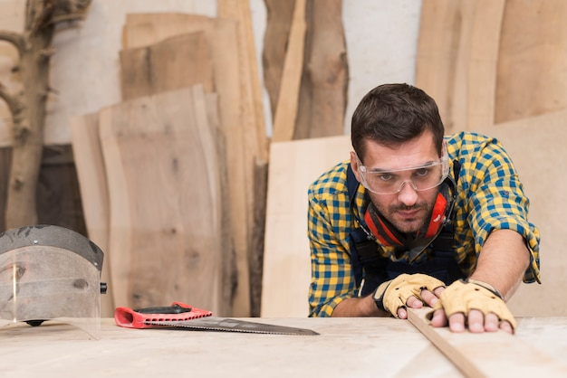 Close-up of a male carpenter working in the workshop Free Photo