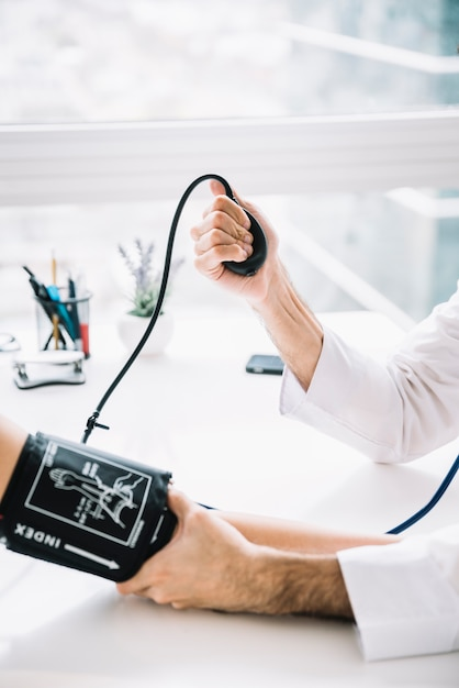 Close-up of a male doctor hand measuring blood pressure of patient in clinic Free Photo