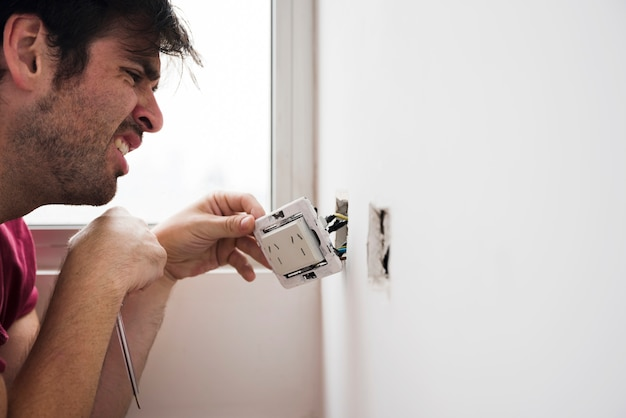 Close-up of male electrician working at home Free Photo