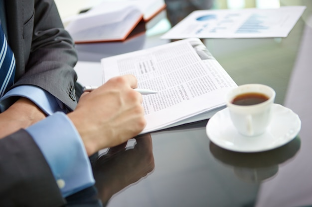 Close-up of male executive reading news Free Photo